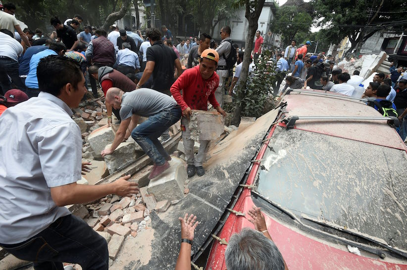 People remove debris of a building which collapsed after a quake rattled Mexico City on September 19, 2017. A powerful earthquake shook Mexico City on Tuesday, causing panic among the megalopolis' 20 million inhabitants on the 32nd anniversary of a devastating 1985 quake. The US Geological Survey put the quake's magnitude at 7.1 while Mexico's Seismological Institute said it measured 6.8 on its scale. The institute said the quake's epicenter was seven kilometers west of Chiautla de Tapia, in the neighboring state of Puebla. / AFP PHOTO / Alfredo ESTRELLA (Photo credit should read ALFREDO ESTRELLA/AFP/Getty Images)