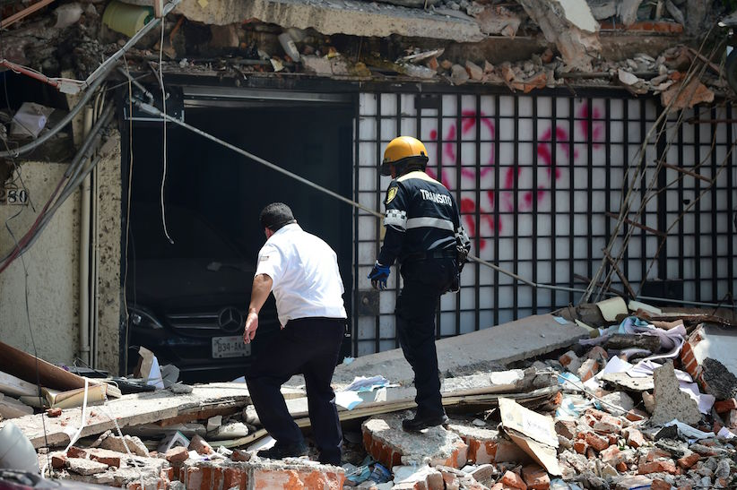 A traffic controller and a security guard look for possible victims at a building which collapsed during a quake in Mexico City on September 19, 2017. A powerful earthquake shook Mexico City on Tuesday, causing panic among the megalopolis' 20 million inhabitants on the 32nd anniversary of a devastating 1985 quake. The US Geological Survey put the quake's magnitude at 7.1 while Mexico's Seismological Institute said it measured 6.8 on its scale. The institute said the quake's epicenter was seven kilometers west of Chiautla de Tapia, in the neighboring state of Puebla. / AFP PHOTO / Ronaldo SCHEMIDT (Photo credit should read RONALDO SCHEMIDT/AFP/Getty Images)