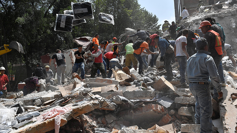 People remove debris of a collapsed building looking for possible victims after a quake rattled Mexico City on September 19, 2017. A powerful earthquake shook Mexico City on Tuesday, causing panic among the megalopolis' 20 million inhabitants on the 32nd anniversary of a devastating 1985 quake. The US Geological Survey put the quake's magnitude at 7.1 while Mexico's Seismological Institute said it measured 6.8 on its scale. The institute said the quake's epicenter was seven kilometers west of Chiautla de Tapia, in the neighboring state of Puebla. / AFP PHOTO / Omar TORRES (Photo credit should read OMAR TORRES/AFP/Getty Images)
