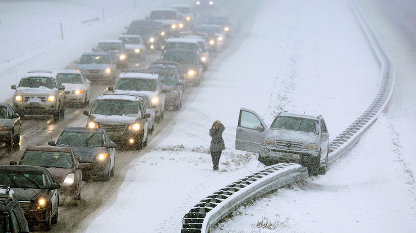 A woman uses a cell phone after climbing out of a vehicle that ended up on a guard rail in the median of Interstate 295 during a snow storm in Cumberland, Maine, Friday, Feb. 25, 2011. (AP Photo/Robert F. Bukaty)