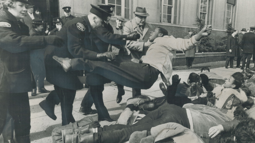 Police force a black youth to the ground. He was among about 80 student demonstrators who marched on the U.S. consulate on University Ave. to back civil rights workers in Alabama on March 16, 1966. (Gerry Barker/Toronto Star/Getty Images)