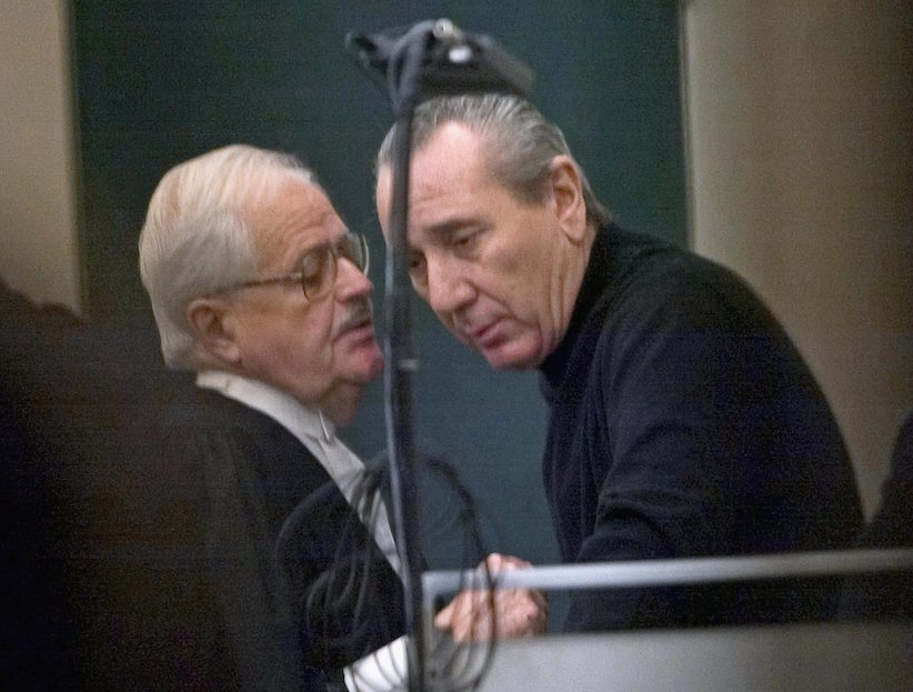 Vito Rizzuto (right), the reputed head of the Montreal Mafia, speaks with his attorney Jean Salois after his hearing in Montreal on Feb. 6, 2004. (Ryan Remiorz/CP)