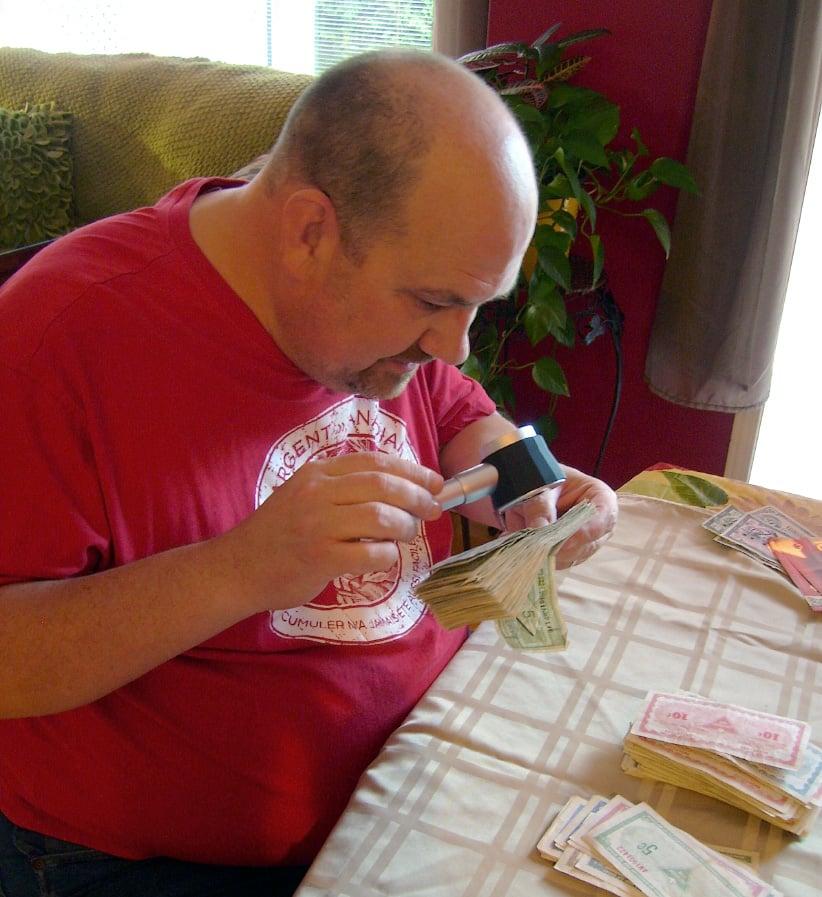 Marc-André Lemire inspecting his Canad Tire money collection. (Milva Salera)