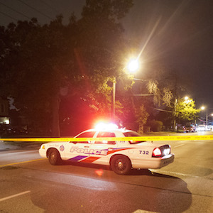 A man watches on at a crime scene following a shooting in Scarborough, a suburb in east Toronto, July 17, 2012.  Two people were killed and at least 19 injured in a shooting at an outdoor party in Toronto, police said on Tuesday, raising fresh fears of a rise in gun crime in Canada's largest city. REUTERS/Mark Blinch (CANADA - Tags: CRIME LAW) - GM1E87H18W101