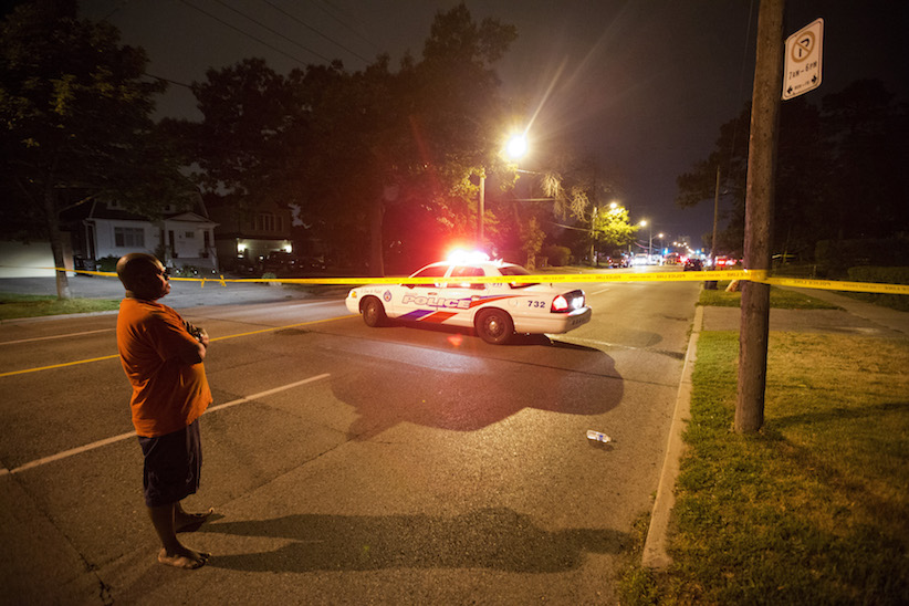 A man watches on at a crime scene following a shooting in Scarborough, a suburb in east Toronto, July 17, 2012. Two people were killed and at least 19 injured in a shooting at an outdoor party in Toronto, police said on Tuesday. (Mark Blinch/Reuters)