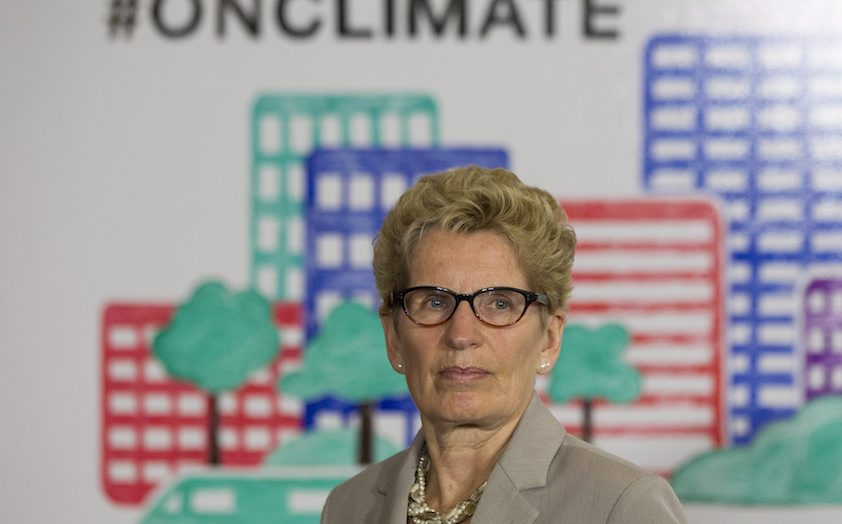 Ontario Premier Kathleen Wynne listens to questions from the media during an announcement which outlined a cap and trade deal with Quebec aimed at curbing green house emissions, in Toronto on Monday, April 13 2015. The plan involves government-imposed limits on emissions from companies, and those that want to burn more fossil fuels can buy carbon credits from those that burn less than they are allowed. THE CANADIAN PRESS/Chris Young