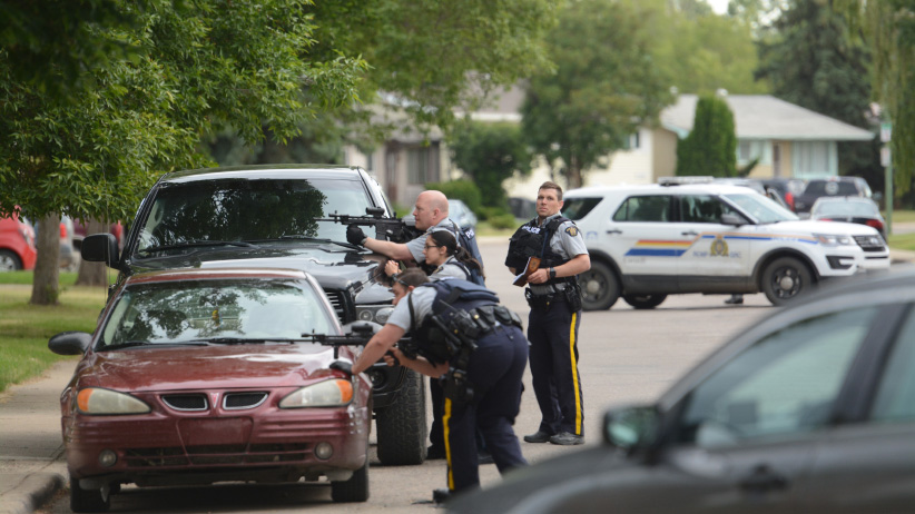 Police take cover behind vehicles with guns drawn during standoff in North Battleford in June, 2017. (Greg Higgins/battlefordsNOW)