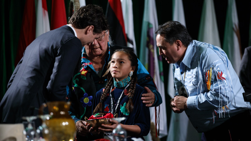 Autumn Peltier presents Prime Minister Trudeau with a water bundle at the Assembly of First Nations annual meeting in Gatineau. December 6, 2016. (Adam Scotti/PMO)