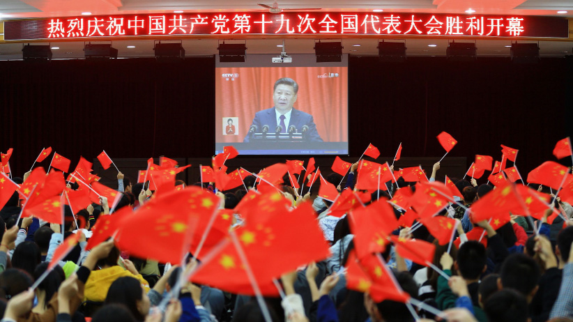 """College students wave national flags as they watch the opening of the 19th Communist Party Congress in Huaibei in China's eastern Anhui province on October 18, 2017. President Xi Jinping declared China is entering a """"new era"""" of challenges and opportunities on October 18, as he opened a Communist Party congress expected to enhance his already formidable power. (AFP/Getty Images)"""