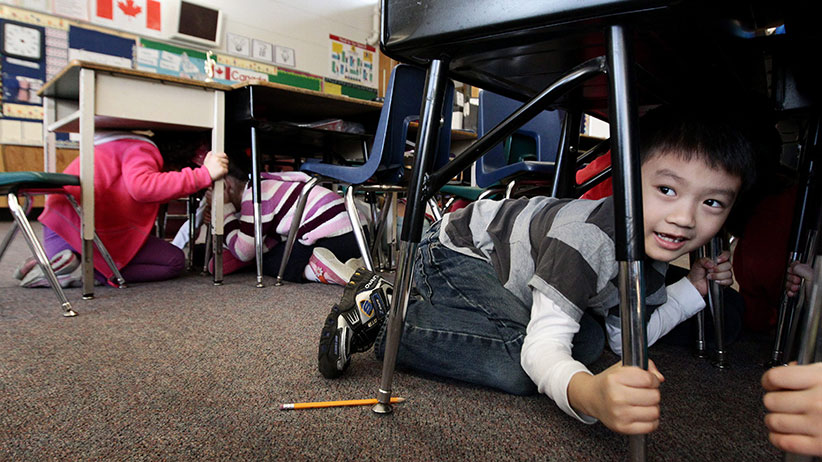 """Grade one student, six-year-old Joseph Kim, takes cover under his desk during an earthquake drill at Hollyburn Elementary School in West Vancouver, B.C., on Wednesday January 26, 2011. More than 400,000 British Columbians took part in the drill called """"ShakeOut"""" simultaneously at schools and businesses across the province in the largest earthquake-preparedness program ever held in Canada. (Darryl Dyck/CP)"""
