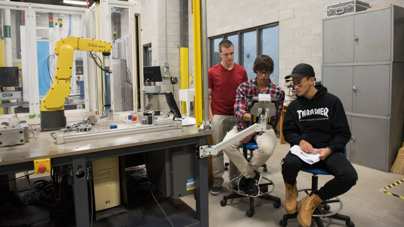 Nathan Wells, left, Jake Mihkelson, and Zhenlin Wangat work on a robot at Conestoga College in an Introduction to Robotics lab in Cambridge, Ontario. (Photograph by Hannah Yoon)
