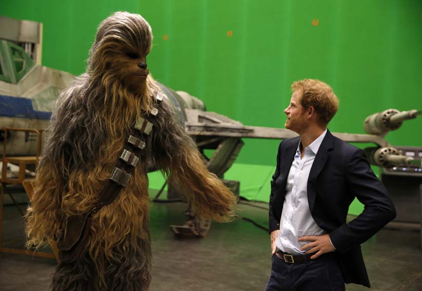 April 19, 2016: Prince Harry meets 'Star Wars' character Chewbacca during a visit to the set at Pinewood studios in England. (Adrian Dennis/Getty Images)