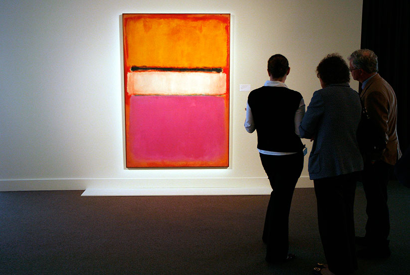 """People view a painting titled """"White Center (Yellow, Pink and Lavender on Rose)"""" by Mark Rothko. (Chip East/Reuters)"""