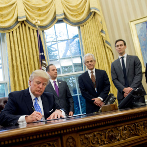US President Donald Trump signs an executive order alongside White House Chief of Staff Reince Priebus (C), US Vice President Mike Pence (L), National Trade Council Advisor Peter Navarro (3rd R), Senior Advisor Jared Kushner (2nd R) and Senior Policy Advisor Stephen Miller in the Oval Office of the White House in Washington, DC, January 23, 2017. Trump on Monday signed three orders on withdrawing the US from the Trans-Pacific Partnership trade deal, freezing the hiring of federal workers and hitting foreign NGOs that help with abortion. (Saul Loeb/AFP/Getty Images)
