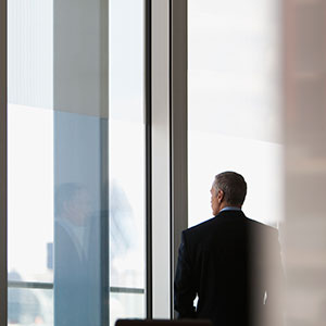 Businessman looking out conference room window. (Tom Merton/Getty Images)