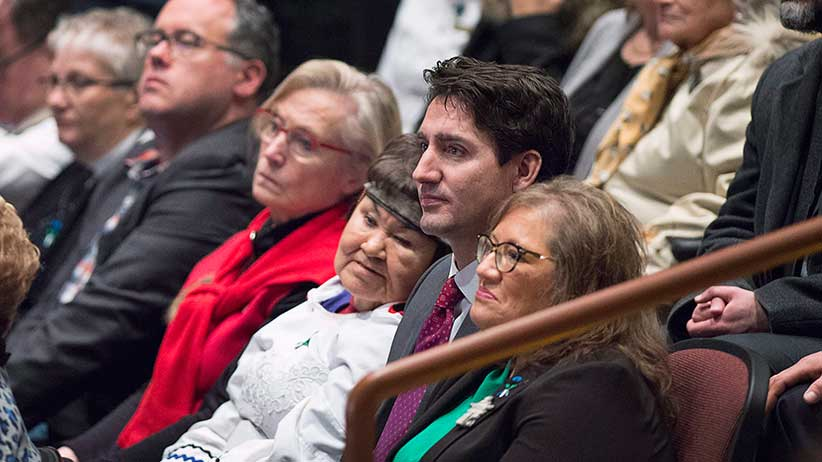Prime Minister Justin Trudeau sits in the crowd before he delivered an apology on behalf of the Government of Canada to former students of the Newfoundland and Labrador Residential Schools in Happy Valley-Goose Bay, N.L. on Friday, Nov. 24, 2017. THE CANADIAN PRESS/Andrew Vaughan