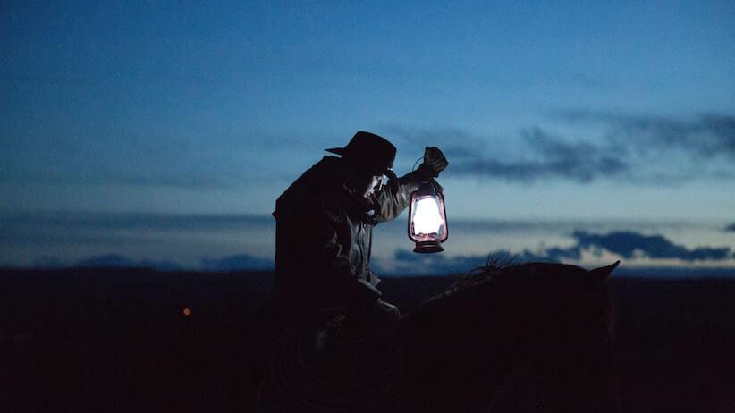 Cowboy on horse with lantern at dusk