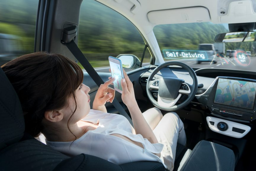 Woman using phone while sitting in the driver's seat of self-driving cars