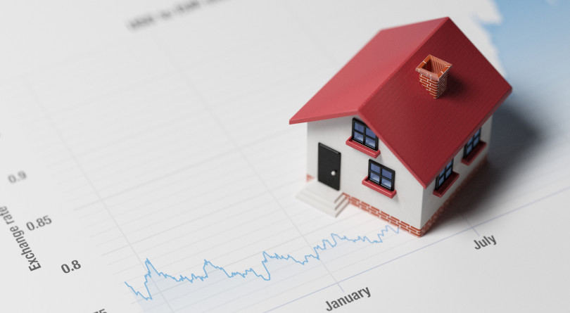 Miniature House on A Blue Financial Graph representing investing in real estate