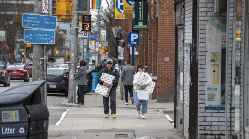Shoppers carrying toilet paper in Toronto, on March 20, 2020 (CP/Dominic Chan)