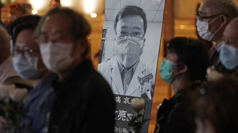 In this Feb. 7, 2020, file photo, people wearing masks attend a vigil for Chinese doctor Li Wenliang, who was reprimanded for warning about the outbreak of the new coronavirus, in Hong Kong. China has taken the highly unusual move of exonerating the doctor who was reprimanded for warning about the coronavirus outbreak and later died of the disease. An official media report said police in Wuhan had revoked its admonishment of Dr. Li that had included a threat of arrest and issued a solemn apology