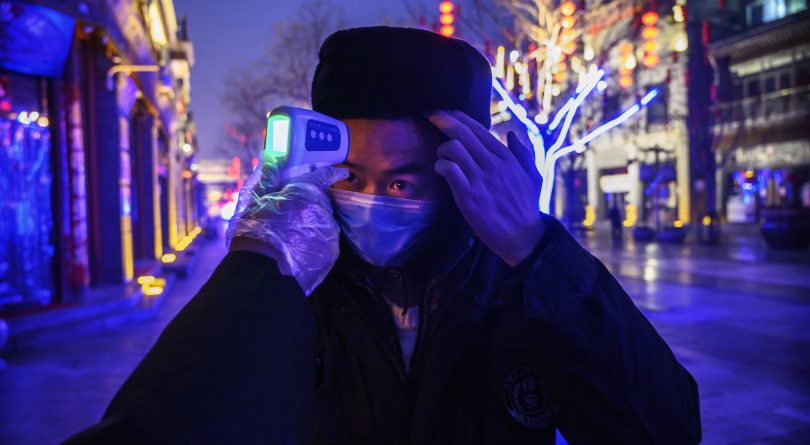 A pedestrian in Beijing has his temperature checked (Kevin Frayer/Getty Images)