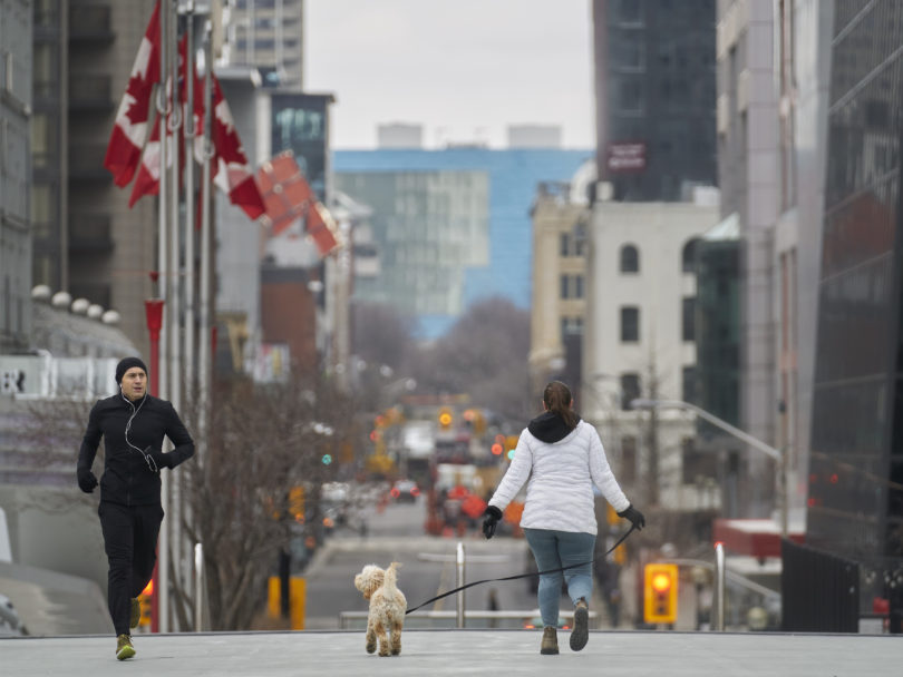 A jogger keeps his distance from a woman walking her dog in downtown Toronto, Ontario on March 24, 2020. - The province of Ontario has set a deadline of midnight Tuesday for all non-essential businesses to close due to the Covid-19 outbreak. Prime Minister Justin Trudeau's online plea for people to stay home during the coronavirus pandemic has gone viral, with actor Ryan Reynolds, musician Michael Buble and other Canadian celebrities on Tuesday helping to spread the word. (Photo by Geoff Robins / AFP) (Photo by GEOFF ROBINS/AFP via Getty Images)
