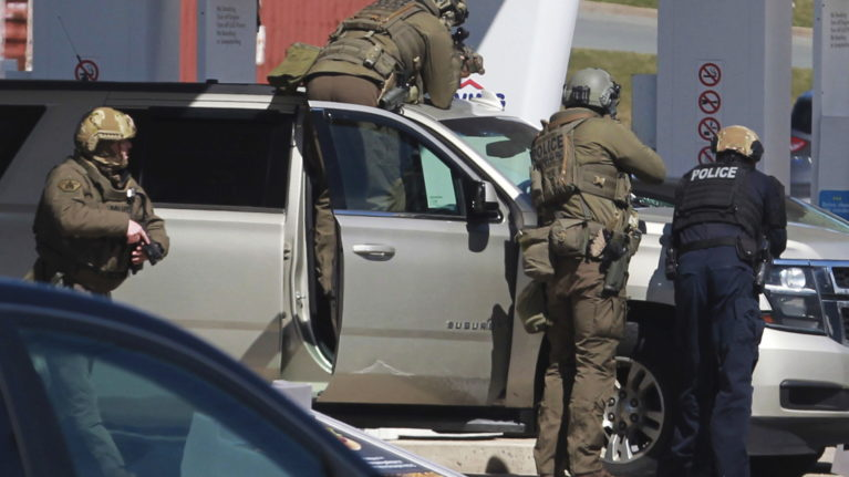 RCMP officers surround a suspect at a gas station in Enfield, N.S., on April 19, 2020 (Tim Krochak/The Canadian Press via AP, File)