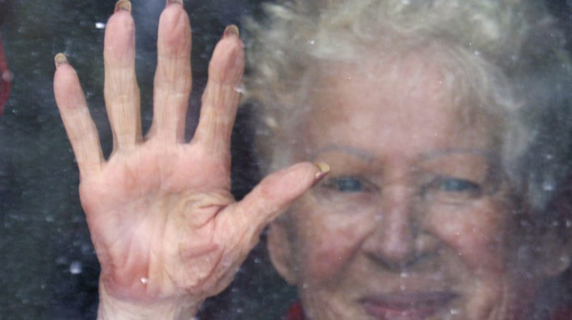 Resident Adeline Thrush, age 84, touches her window to acknowlege family and local residents showing up outside each afternoon to show caring and support for residents in isolation at a long term care centre in Calgary, Alberta on Apr. 2, 2020. (Larry MacDougal/CP)