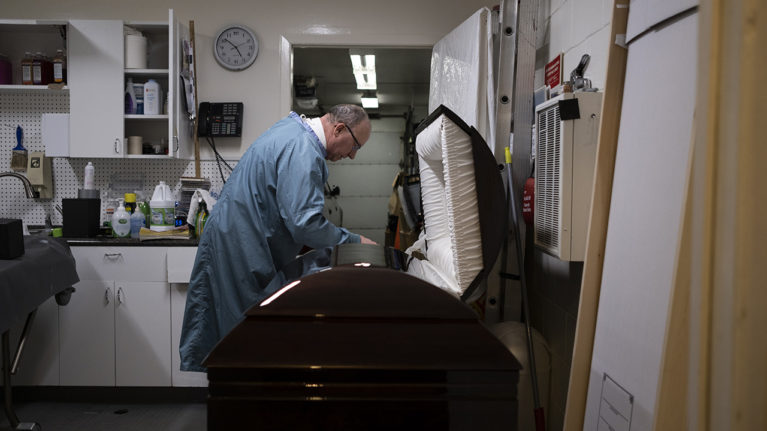 Funeral Director RIchard Paul adjusts a body in a casket. (Photograph by Isaac Paul)