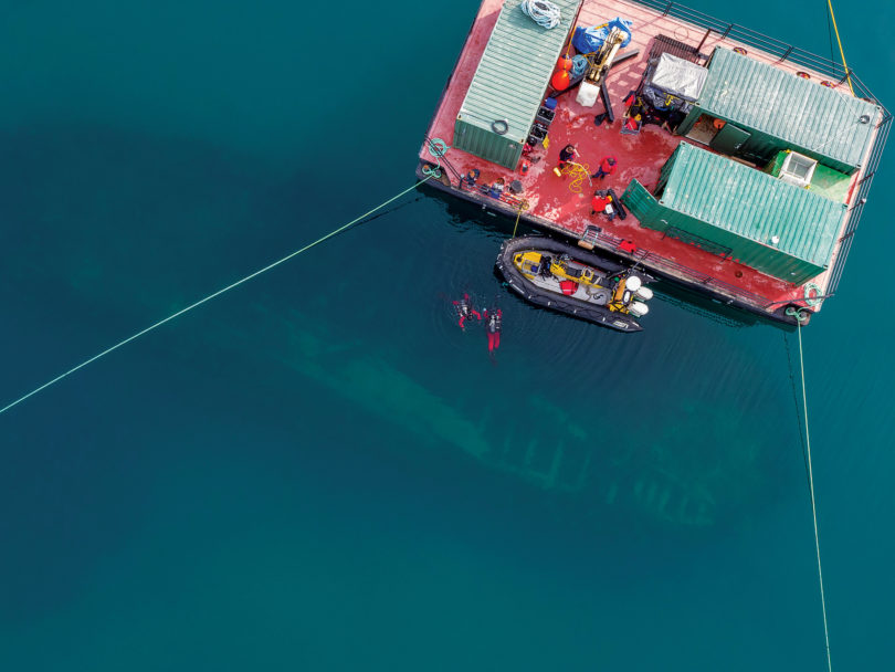 Qiniqtiryuaq (barge) above the Erebus site, wreck and divers visible.(Courtesy of Parks Canada)