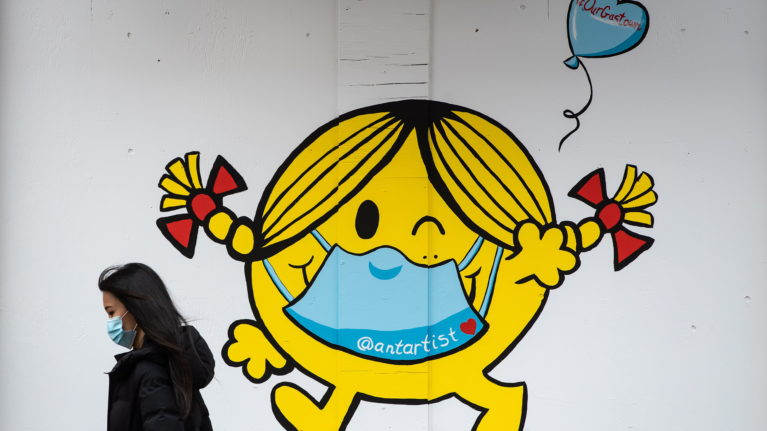 A mural in Vancouver shows author and illustrator Roger Hargreaves's Little Miss Sunshine character wearing a face mask (Darryl Dyck/CP)