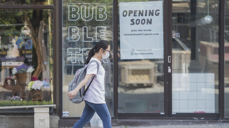 A woman wears a face mask as she walks along Sainte-Catherine street in Montreal, Sunday May 24, 2020, as the COVID-19 pandemic continues in Canada and around the world. Stores with a street entrance are allowed to reopen in Montreal on May 25th. THE CANADIAN PRESS/Graham Hughes