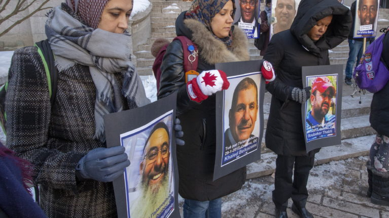 People hold photos of the victims during a vigil on Jan. 29, 2020 in Montreal to commemorate the third anniversary of the mosque shooting in Quebec City that left six people dead. (Ryan Remiorz/CP)