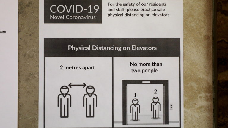 A sign urging physical distancing when using elevators is seen in a high-rise building in downtown Toronto on May 8, 2020. (Colin Perkel/CP)