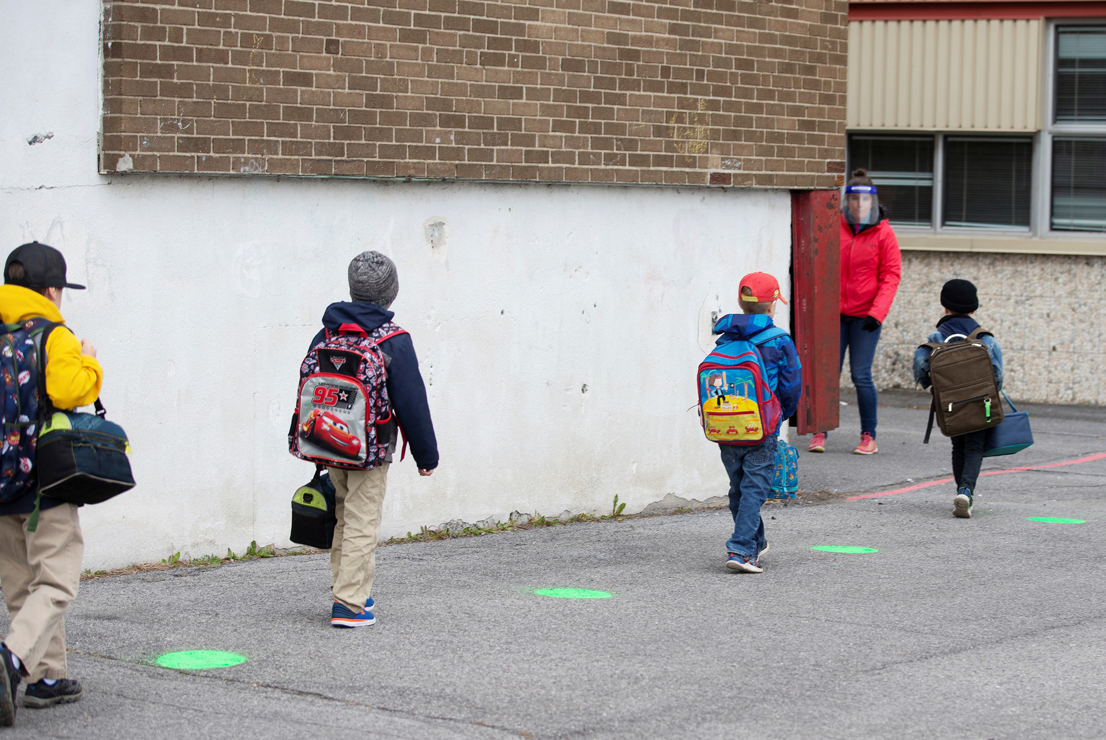 Children in Saint-Jean-sur-Richelieu, Que., use green dots painted on the tarmac to help maintain proper social distancing; schools outside the greater Montreal area began to reopen in mid-May as the COVID-19 pandemic wore on, and children were asked to adapt to new realities (Christinne Muschi/Reuters)
