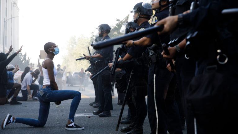 A young woman takes a knee in front of police officers during a protest in San Jose, Calif., on May 29 (Dai Sugano/MediaNews Group/The Mercury News/Getty Images)