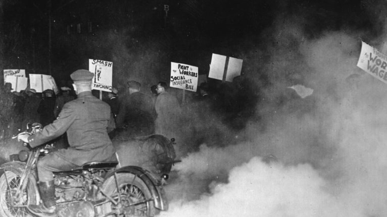 New York police on motorcycles wrap a demonstration in fog to prevent the demonstrators at the march-past in front of a building in which President Herbert Hoover is speaking in New York, 1930. (Photo by Imagno/Hulton Archive/Getty)