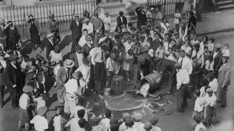 Beer is dumped into the street by police officers on Sep 13, 1929 after police discovered a home-brewed in a home. (NY Daily News Archive/Getty Images)