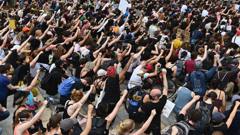 Protesters kneel and raise their fists during a Black Lives Matter demonstration in Brooklyn, N.Y. (Angela Weiss/AFP/Getty Images)