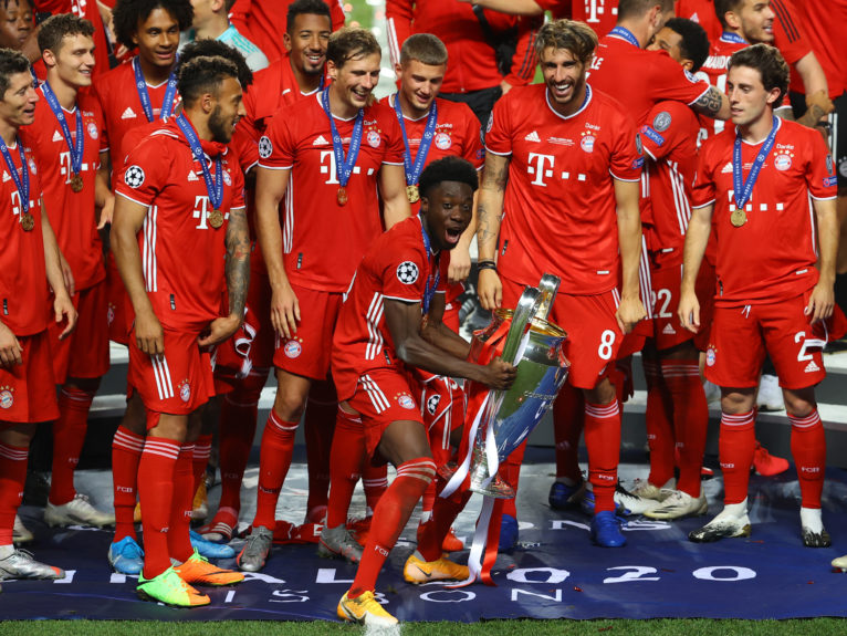 Alphonso Davies of FC Bayern Munich celebrates with the UEFA Champions League Trophy following his team's victory in the UEFA Champions League Final match between Paris Saint-Germain and Bayern Munich at Estadio do Sport Lisboa e Benfica on August 23, 2020 in Lisbon, Portugal. (Julian Finney/UEFA/Getty Images)