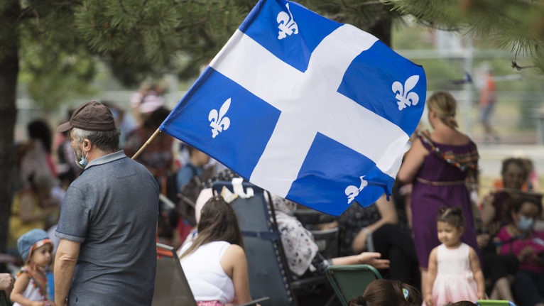 A man holds a Quebec flag as people gather in a city park on St-Jean Baptiste Day in Montreal on June 24, 2020. (Graham Hughes/CP)