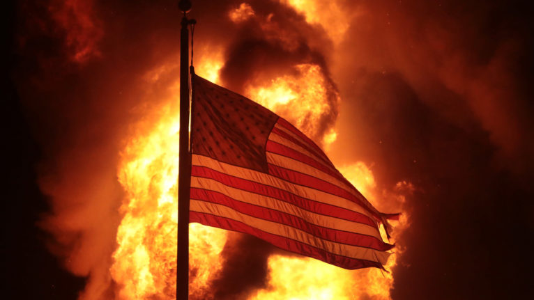 A flag flies outside a burning corrections building during protests and rioting in Kenosha, Wis. (Scott Olson/Getty Images)