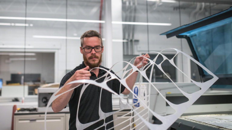 Matt Zeleny, an Applied Research Technologist, removes laser cut PPE face shields at the Camosun Innovates lab. (James MacDonald)