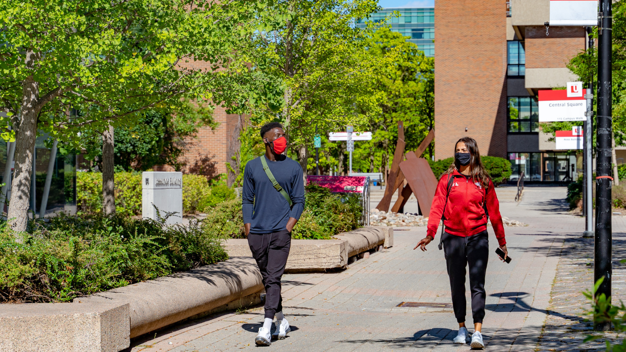 Two students walking on a university campus