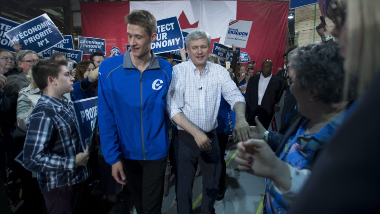 Conservative Leader Stephen Harper greets supporters as son, Ben, centre-left, walks past during a campaign stop in Fredericton, N.B., on Friday, Oct. 16, 2015. (Jonathan Hayward/CP)
