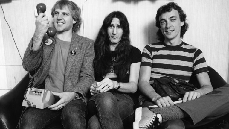 (l-r) Alex Lifeson, Geddy Lee and Neil Peart backstage on Rush's Permanent Waves tour (Fin Costello/Redferns/Getty Images)