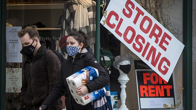 People wears masks as they walk past a store that is closing in Kingston, Ontario on Monday, November 16, 2020, as the COVID-19 pandemic continues across Canada and around the world. (Lars Hagberg/CP)