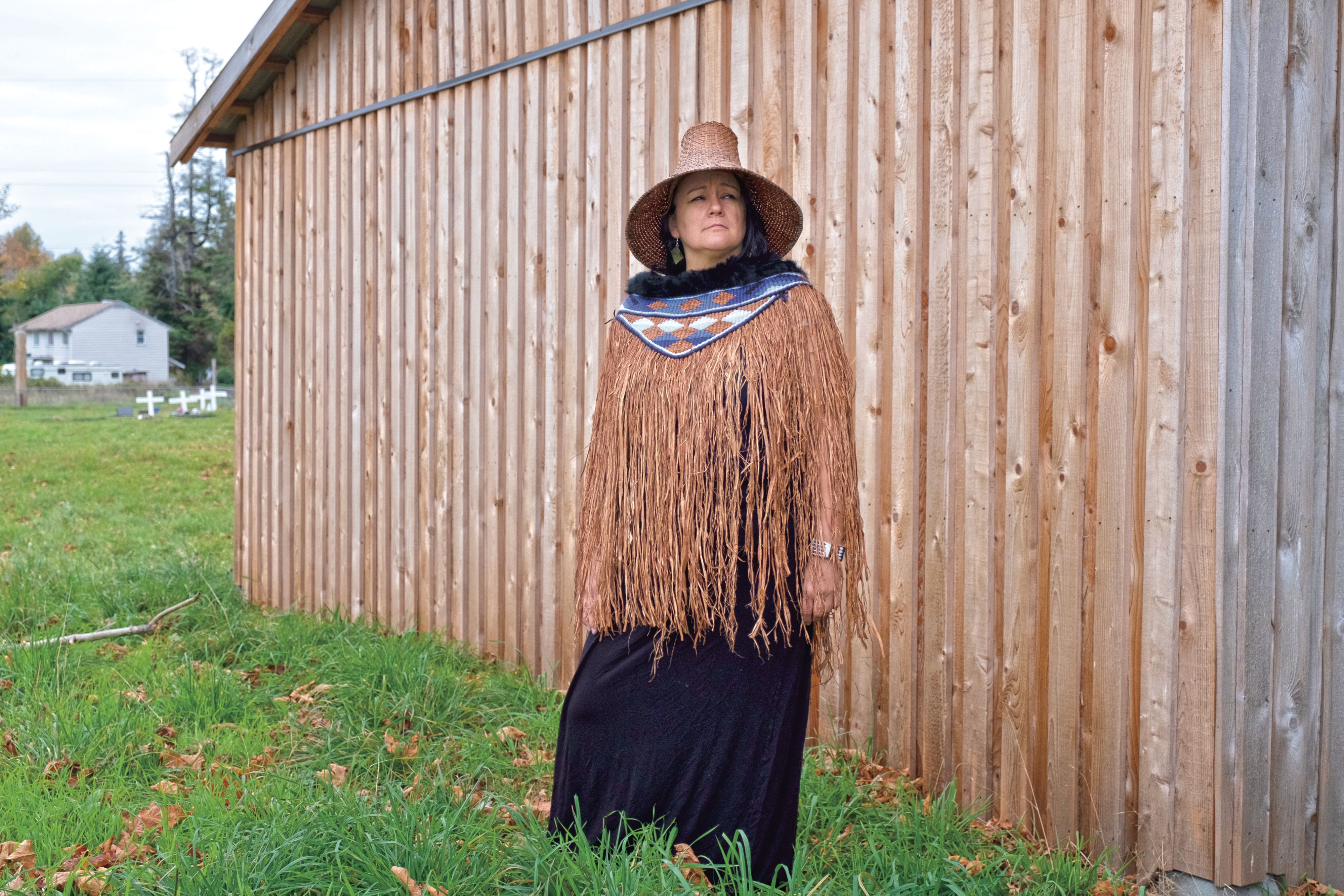 Hegus (Chief) Nicole Rempel of the K'omoks First Nation stands in front of the mortuary house at the K'omoks cemetery. (Photograph by Jen Osborne)
