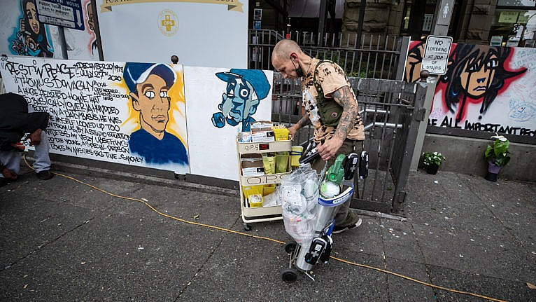 A man wheels oxygen and supplies to a safe injection site in Vancouver's Downtown Eastside (Darryl Dyck/CP)